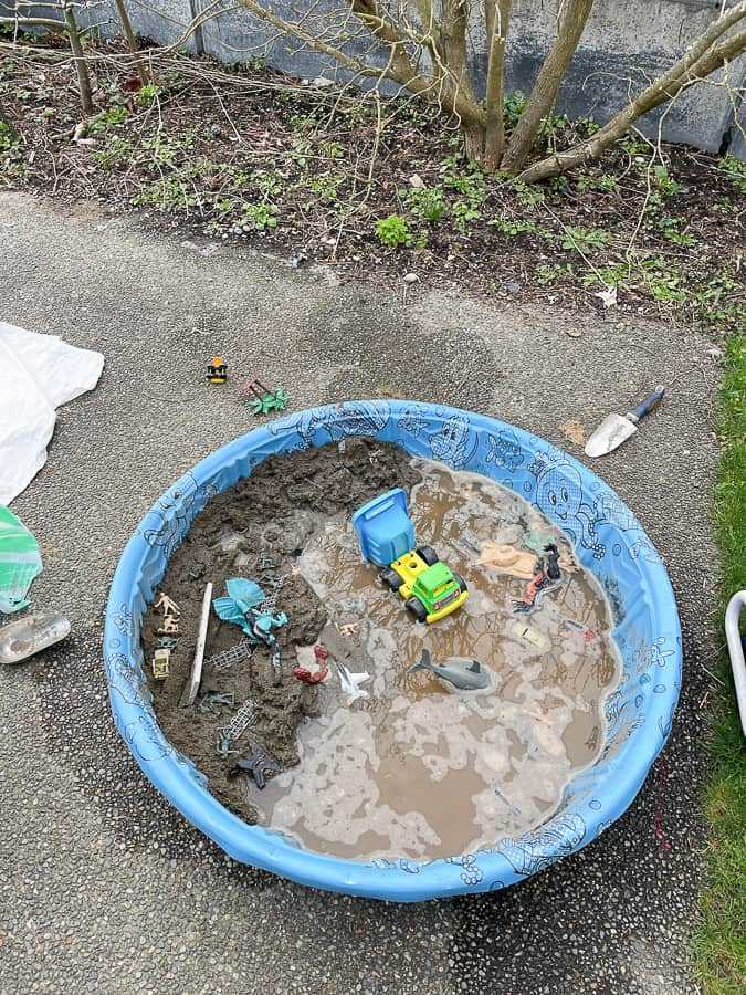 a kiddie pool with mud and toys
