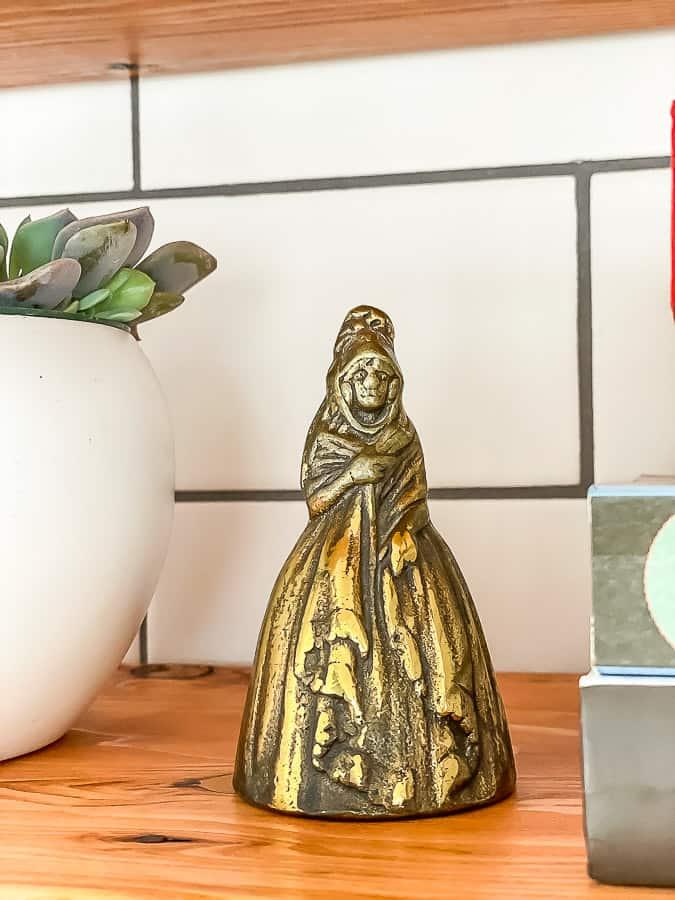 a brass bell on a wooden shelf