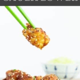 green chopsticks holding a piece of cauliflower tempura