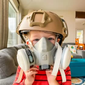 a kid in a battle helmet and gas mask