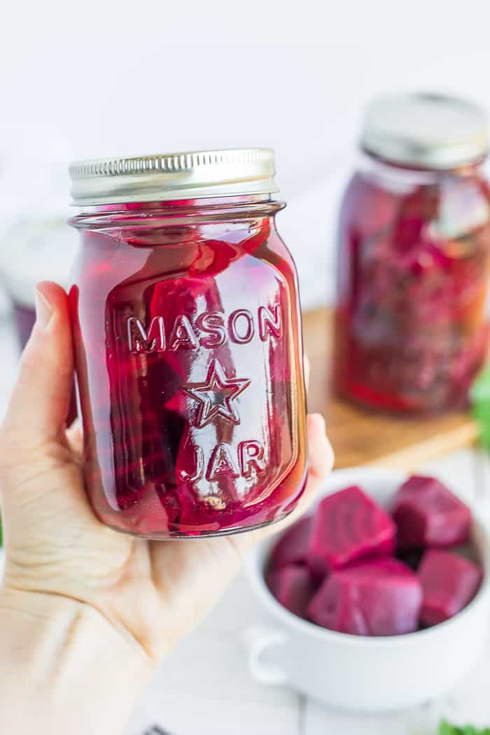 a hand holding a canning jar of beets