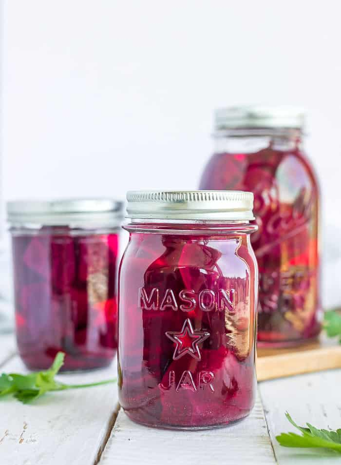 3 canning jars with beets and parsley on a white board