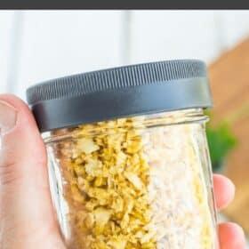 a hand holding dried garlic in a glass jar