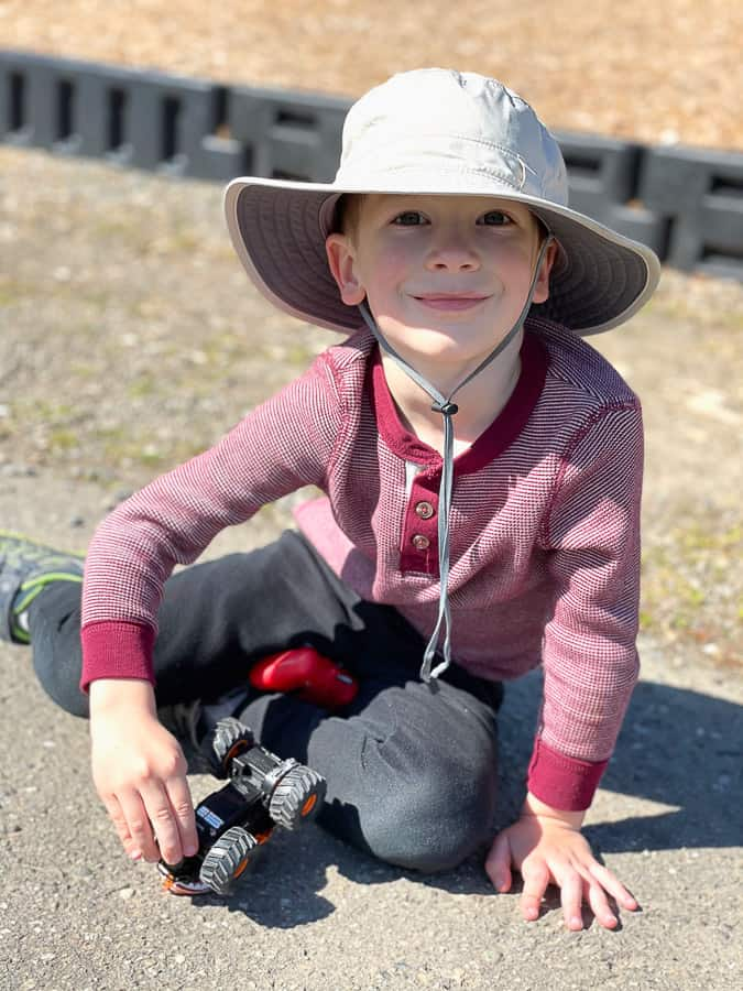 a 5 year old boy in a sun hat holding a monster truck