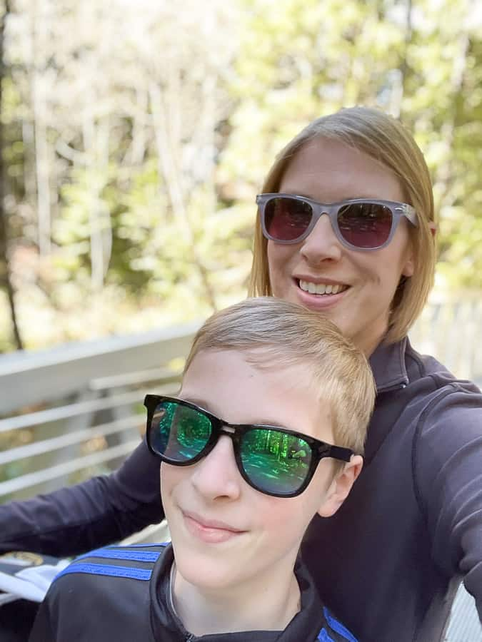 a woman and her son in the woods