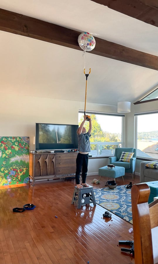 a boy using a grabber to try to reach a balloon