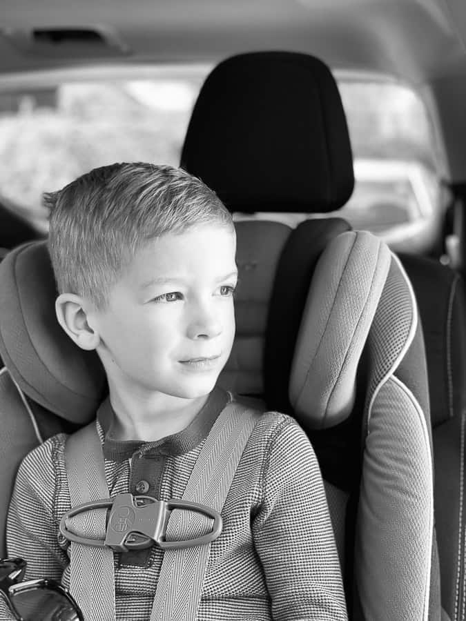 a boy in a carseat looking out the window