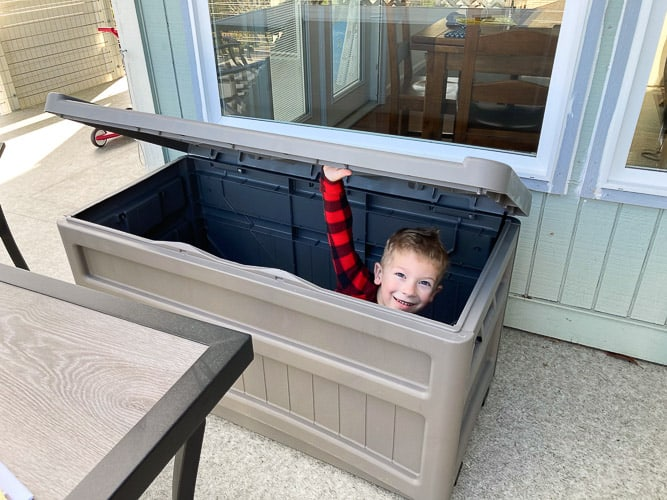 a boy in a deck storage box