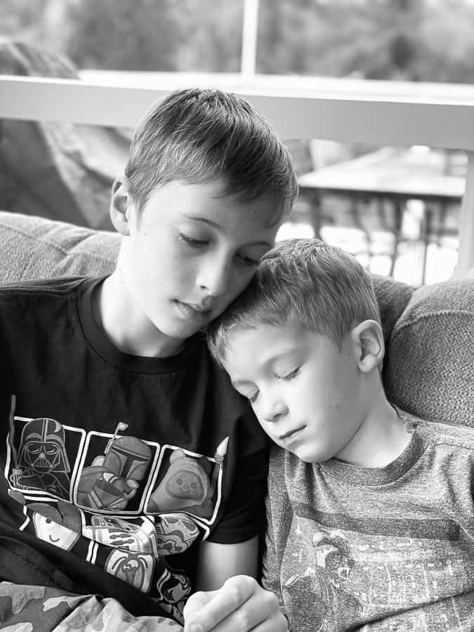 2 brothers in a black and white photo with their heads together