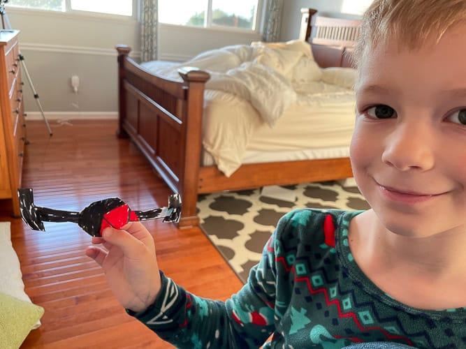 a boy holding a craft in a bedroom