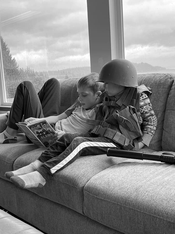 2 brothers on a couch in a black and white photo