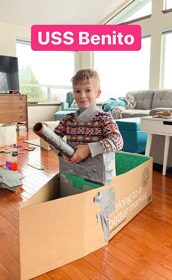 a boy in a cardboard box boat