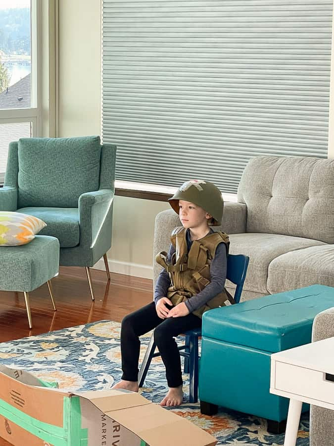 a boy in an army costume sitting on a chair