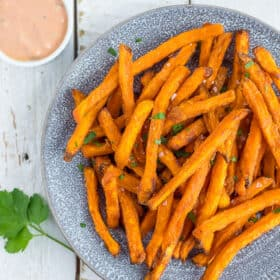 frozen sweet potato fries in an air fryer on a plate