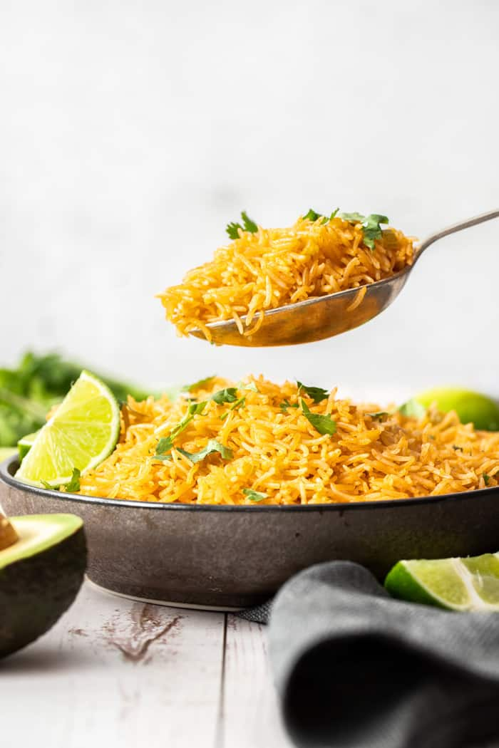 a spoonful of rice being held above a large bowl of rice topped with limes and cilantro
