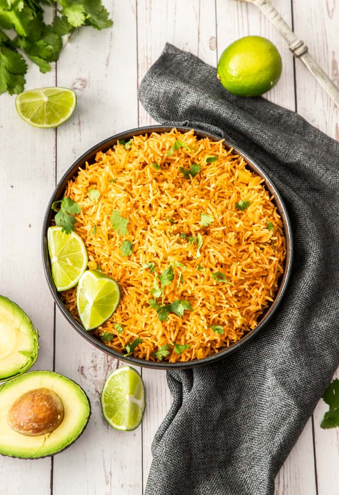 A black bowl filled with Mexican rice and topped with cilantro and limes on a board with avocado and other garnishes