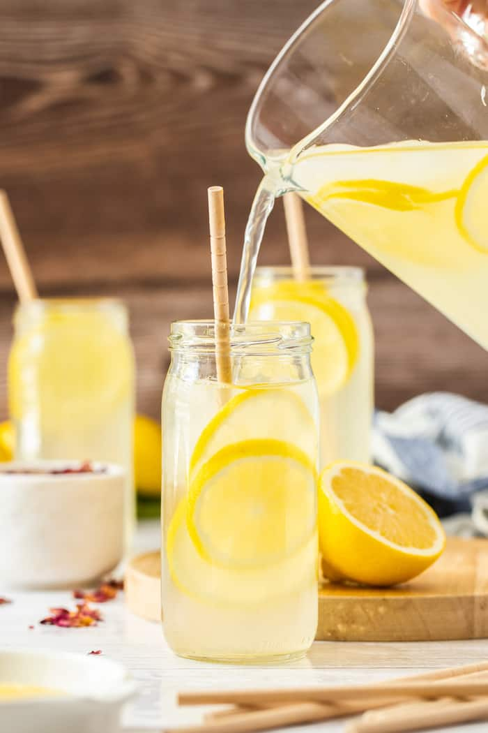 a pitcher of lemonade being poured into a glass with lemons and a straw