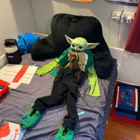 a baby yoda on a bed wearing clothes