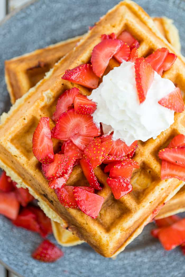 Strawberry topped waffles on a grey plate with whipped cream