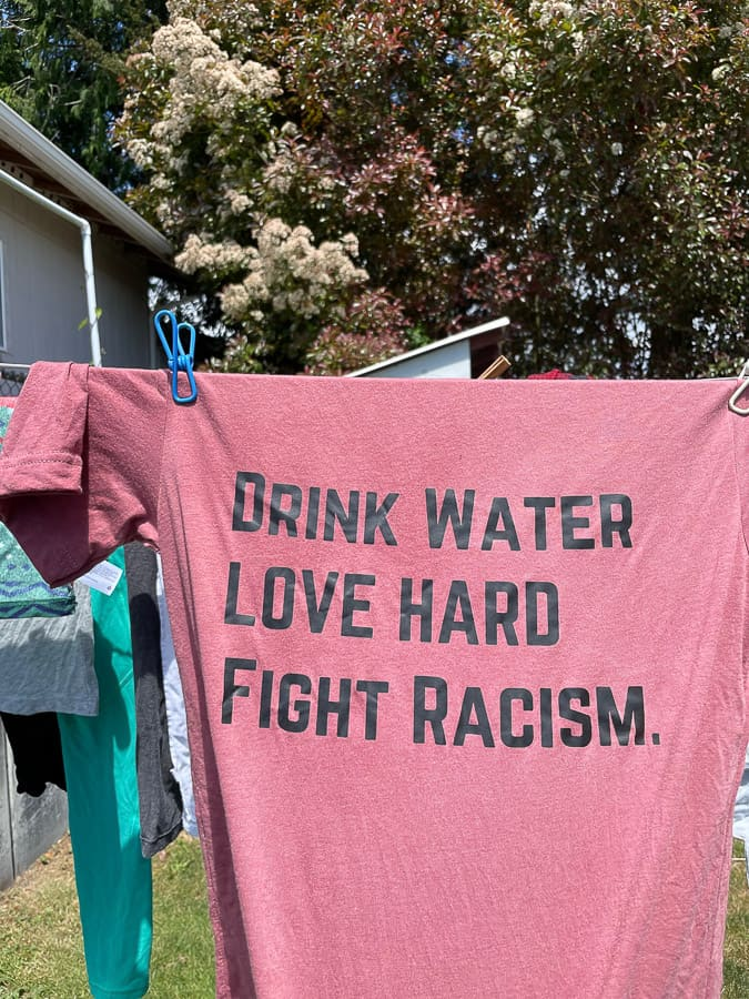 """a pink shirt on a clothesline that says """"Drink Water, Love Hard, Fight Racism"""""""
