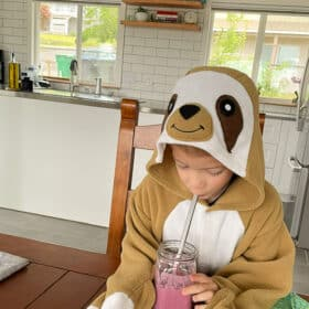 a boy in a sloth costume drinking a smoothie