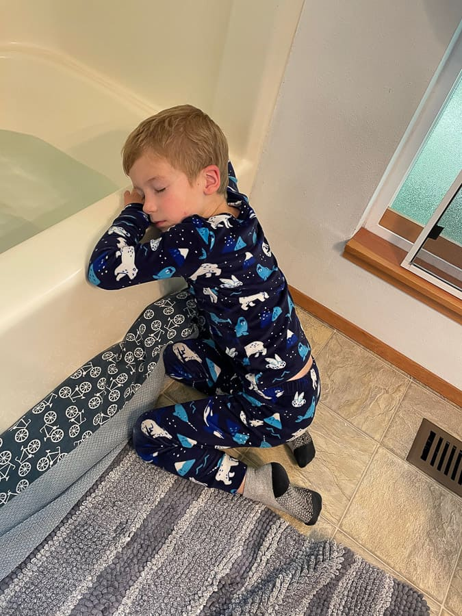 a kid sleeping against a bath tub