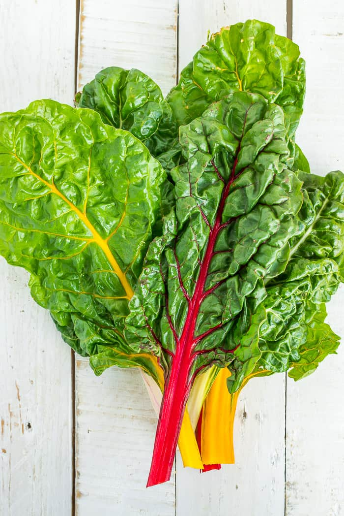 a bunch of rainbow swiss chard on a white board