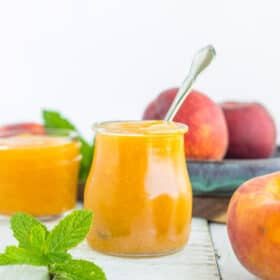a glass jar of peach syrup with a spoon in it on a white wooden board