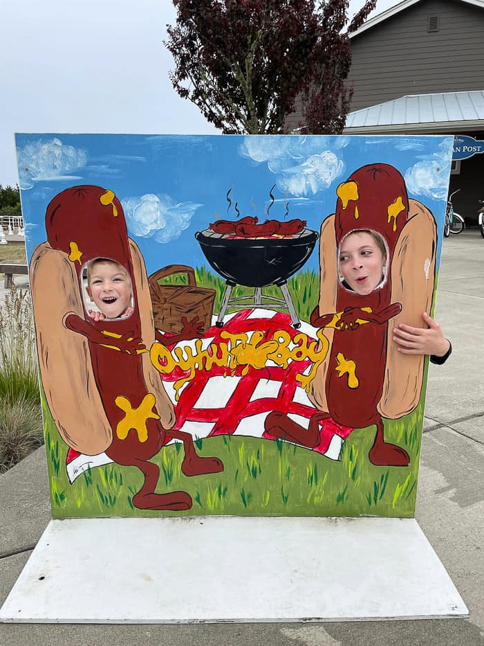 2 boys with their face in a wooden sign