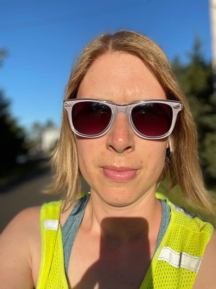 a selfie of a woman in sunglasses and a safety vest
