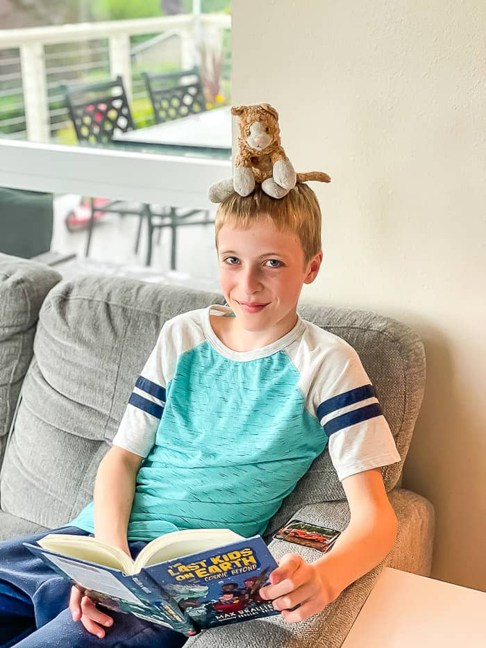 a boy with a stuffed cat on his head