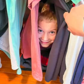 a boy hiding in clothes in a closet