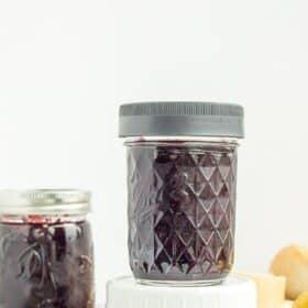 jar of blueberry freezer jam on a white board
