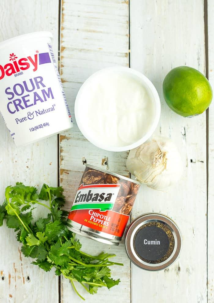 sour cream, greek yogurt, limes, cilantro, garlic, cumin, and canned chipotles on a white board