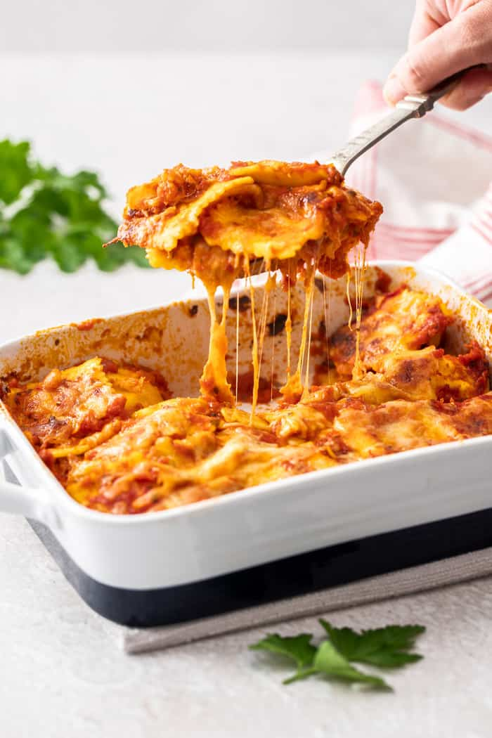 a spatula scooping ravioli lasagna out of a baking dish with cheese stretching