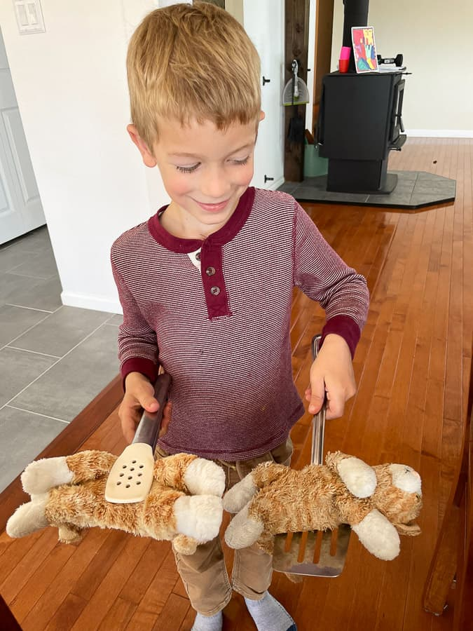 a boy holding 2 stuffed cats on cooking utensils