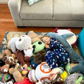 a boy in a pile of stuffed animals