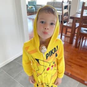a kid in a pikachu costume with a stuffed cat