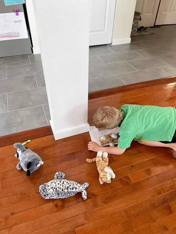 a boy writing on a piece of paper surrounded by stuffed animals