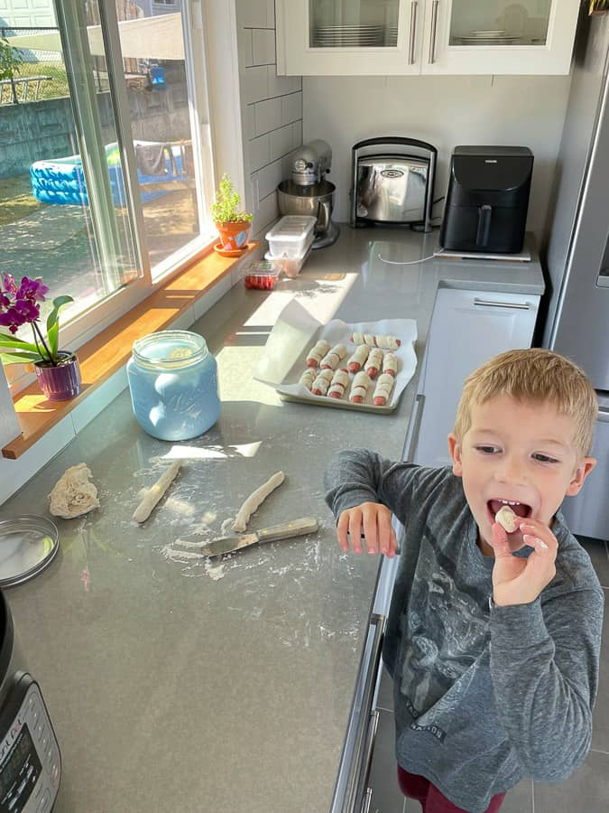 a boy eating dough in a kitchen