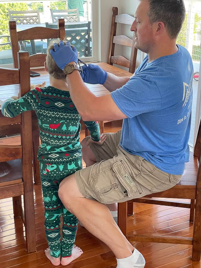 a dad in a blue shirt removing staples from a kid's head