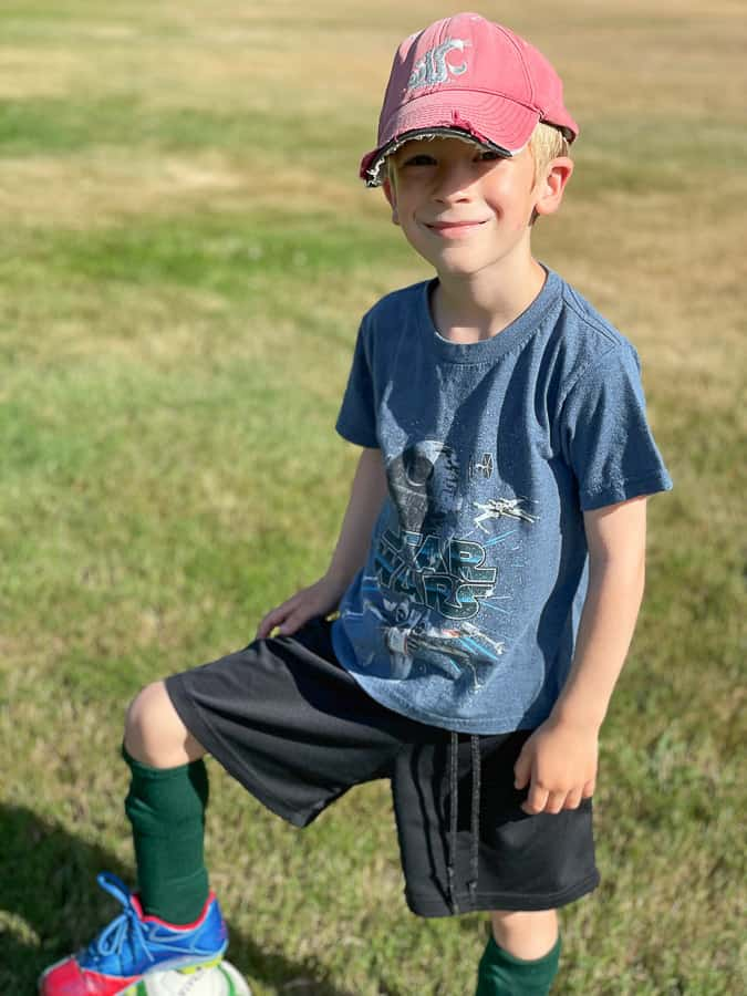 a boy in a red hat with his foot on a soccer ball