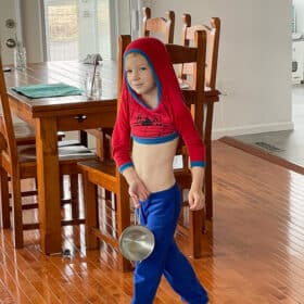 a boy with a shirt over his head carrying a small frying pan