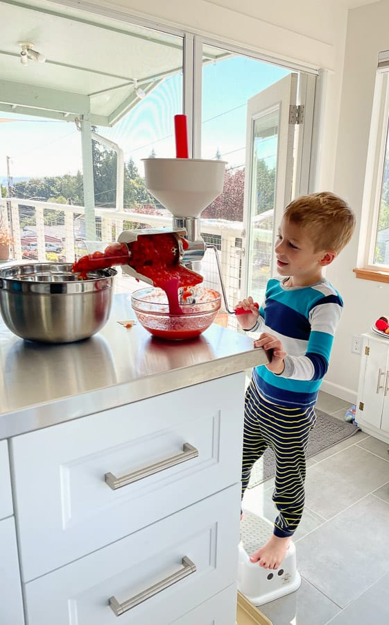 a boy using a food mill with tomatoes