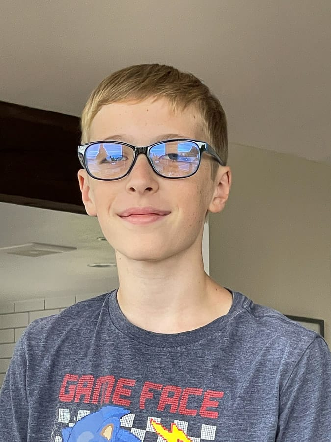 a boy in glasses smiling