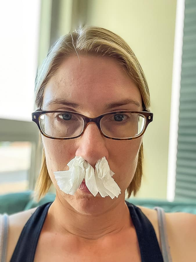 a woman with tissue stuffed in her nose