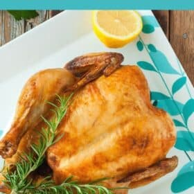 a whole roasted chicken on a plate with rosemary and sliced lemons