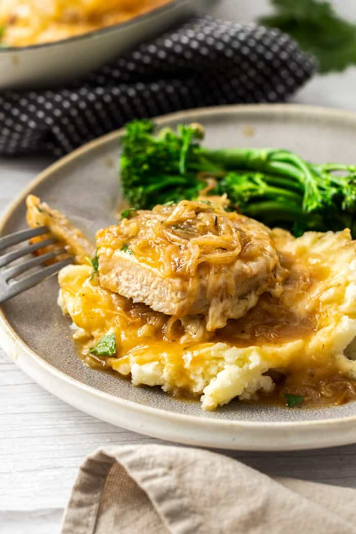 french onion pork chops on a pile of mashed potatoes on a plate