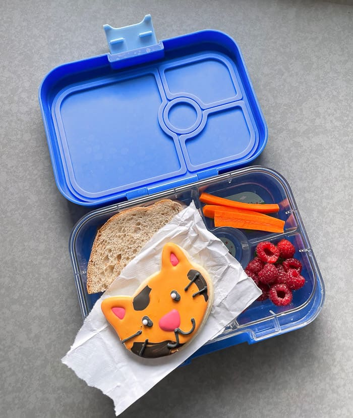 a bento box with a cat cookie and other lunch items