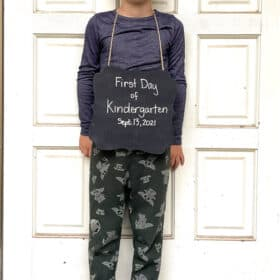 """a boy holding a sign that says """"first day of kindergarten"""" in front of a white door"""